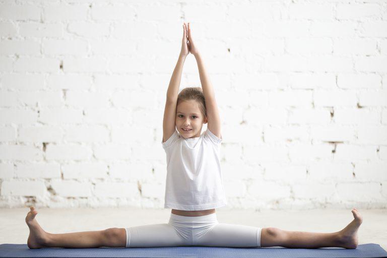 Girl child practicing yoga, doing splits, stretching in Samakonasana exercise, Straight Angle pose, working out wearing sportswear, t-shirt, pants, indoor full length, white studio background